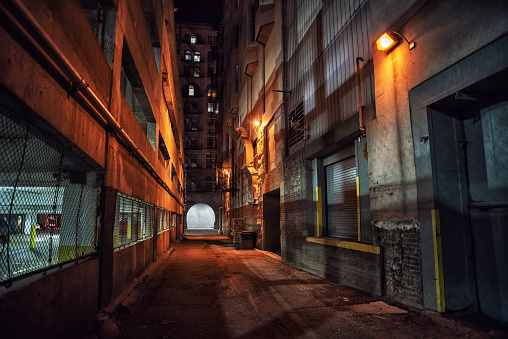 Dark and eerie downtown urban city alley with a loading dock next to a parking garage at night