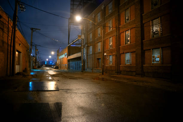 Dark and eerie industrial urban city street at night in Chicago Dark and eerie industrial urban city street at night in Chicago alley stock pictures, royalty-free photos & images