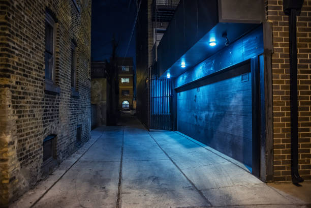 Dark and eerie urban city alley at night stock photo