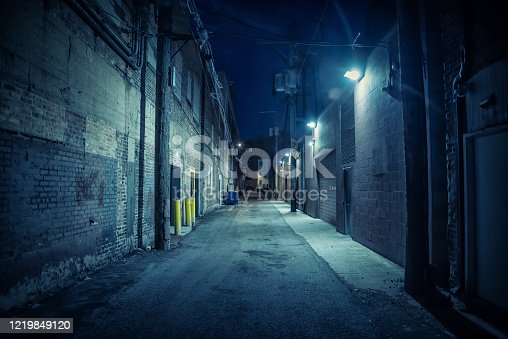 istock Dark and eerie urban city alley at night 1219849120