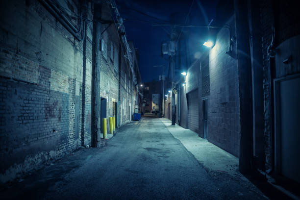 Dark and eerie urban city alley at night Dark and eerie urban city alley at night alley stock pictures, royalty-free photos & images