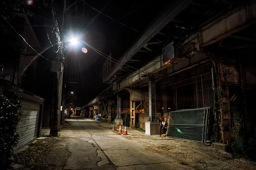 Dark and eerie urban city alley with a vintage railway bridge and construction site at night