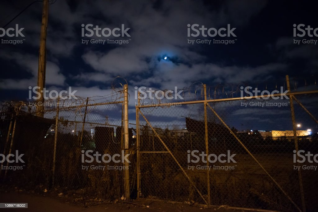 Dark And Gritty Rusty Barbwire Fence Gate By An Abandoned