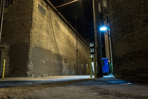 Dark and scary downtown urban city street corner alley with an eerie vintage industrial warehouse factory and a dirty dumpster at night