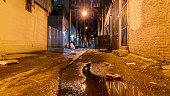istock Dark and scary vintage cobblestone brick city alley at night in Vancouver, British Columbia, Canada. 1192550233