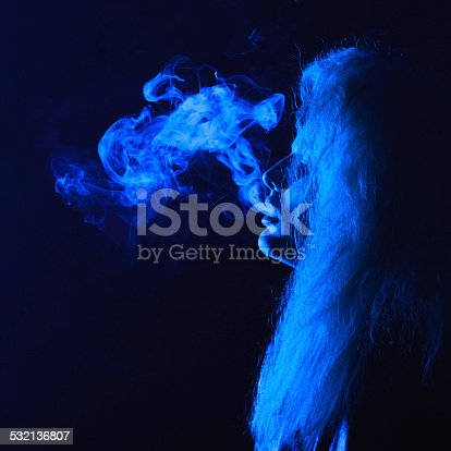 istock dark and sullen shot of a young woman smoking 532136807