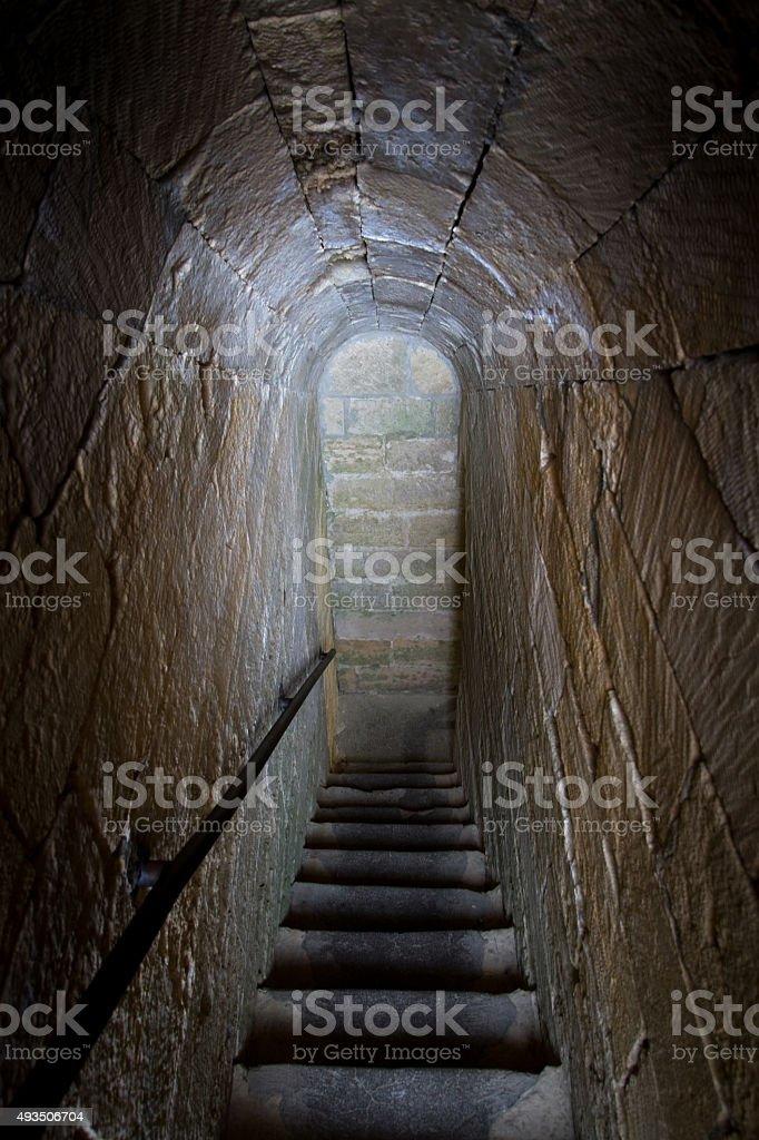 Dark Arched Medieval Narrow Vertigo-Inducing Tunnel-Like Stone Stairway, Italy stock photo