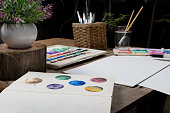 Creative artist workspace with art tools and materials - Wooden desk in an art studio laid out with watercolour paint and brushes with a blank canvas ready for new artwork