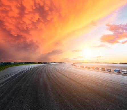 Dark asphalt road circuit and sky at sunset