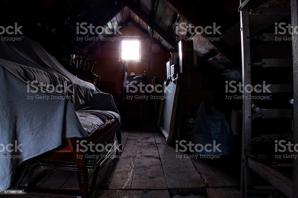 Dark attic with an illuminated window stock photo