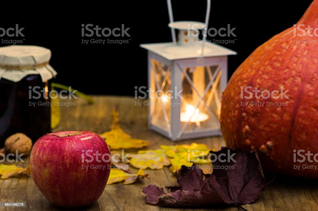 Dark autumn still life with pumpkin, candle and lamp, with yellow leaves of trees on old wooden table board - atmosphere with warm colors royalty-free stock photo