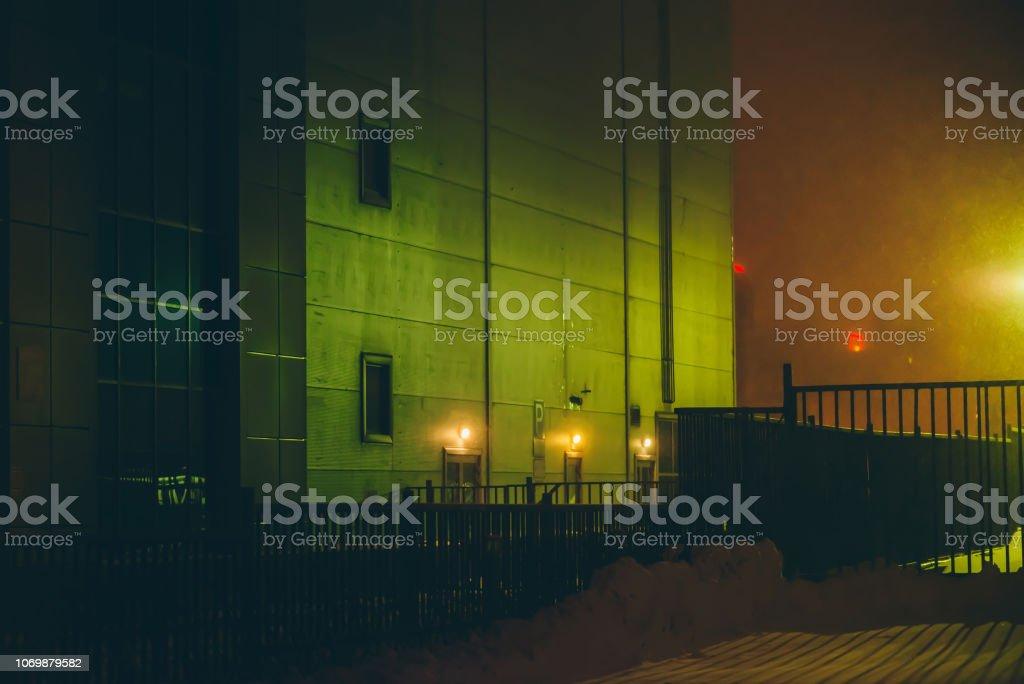 Dark back street with green industrial building in winter night in...