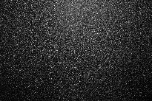 Dark full frame background of hammered powder paint coating on flat sheet steel surface. Also known as hammertone effect.