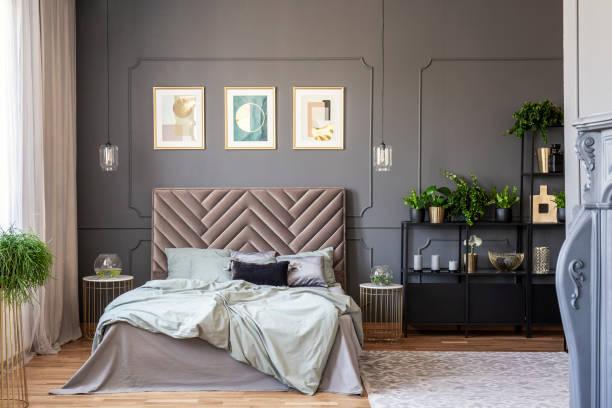 dunkles schlafzimmer innenraum mit einem bequemen doppelbett, gemälden und schwarze regal und wand-spritzgießen - kopfstütze stock-fotos und bilder
