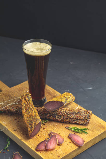 Dark beer in glass and Jerky, basturma, dried meat beef stock photo