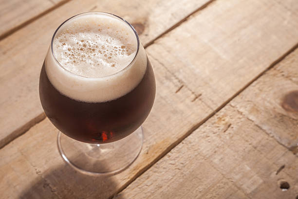 dark beer on wood - dark beer stock photos and pictures