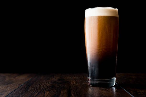 Cerveja escura na superfície de madeira. espaço de cópia. - foto de acervo