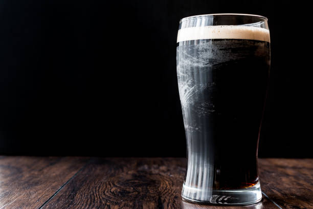 dark beer on wooden surface. - dark beer stock photos and pictures
