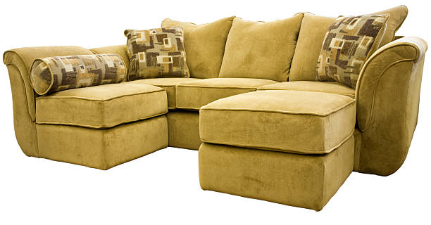 Dark beige sectional sofa with an ottoman and accent pillows stock photo