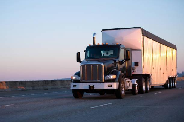 dunkle sattelzug sattelschlepper mit bulk trailer laufen autobahn im abendlicht - autotransporter stock-fotos und bilder