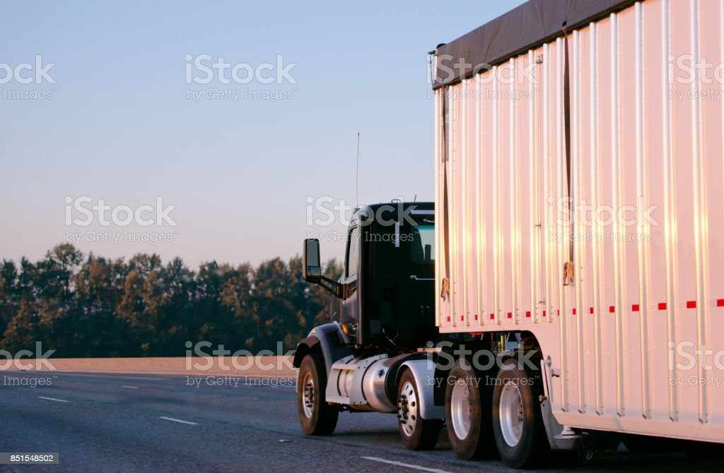 Dark big rig semi truck with day cab carry huge bulk trailer running on interstate highway with commercial cargo stock photo