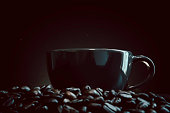 A dark black coffee cup is placed over a pile of roasted coffee beans with a black background and a little sugar bokeh. Photos with space to put text