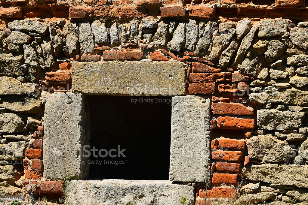 Dark black window in antique brick stone wall royalty free stockfoto
