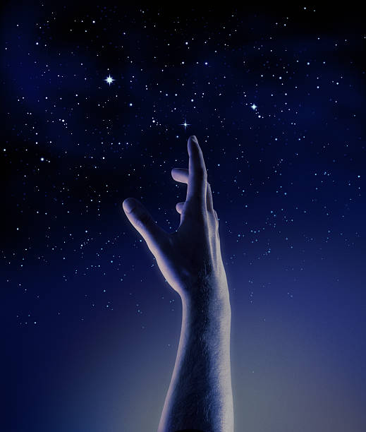 dark blue and black graphic of a hand reaching for stars - nightsky bildbanksfoton och bilder