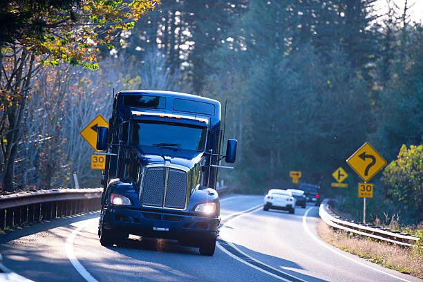 dark blue big rig semi truck on sunny winding highway - aufgemotzte trucks stock-fotos und bilder