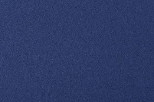Dark blue colored felt texture background on macro