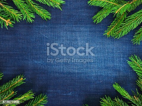Dark blue denim background, shabby, aged in the middle and green spruce branches in the corners. New Year's, Christmas greeting card, free space for an inscription, project.