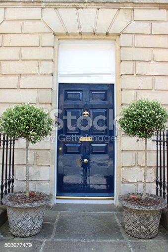 Photo showing a Georgian house / townhouse with a dark blue front door, a Bath stone surround, an old fashioned door bell, and a brass door knocker and letter box. A pair of standard bay trees in large stone pots provide a grand entrance.