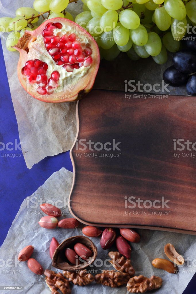 Dark blue grapes, red pomegranate, green grapes, peanuts and walnut on a wooden board with an empty place for writing stock photo