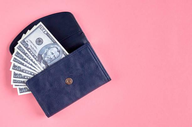 Donkerblauw lederen portemonnee met geld op roze achtergrond compositie. foto