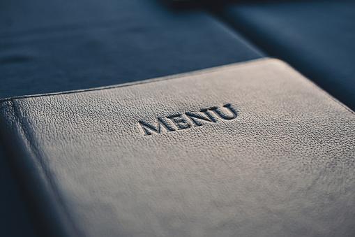 Dark blue menu book on table in restaurant, selective focus