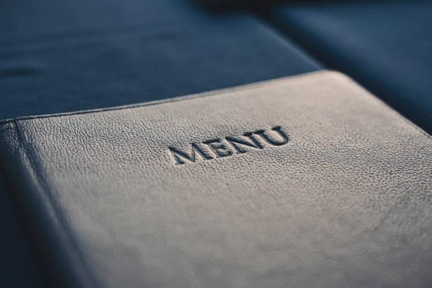 dunkelblaues menübuch auf tisch im restaurant, selektiver fokus - speisekarte stock-fotos und bilder