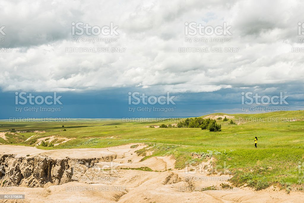 Dark blue rain storm clouds contrast with green prairie stock photo