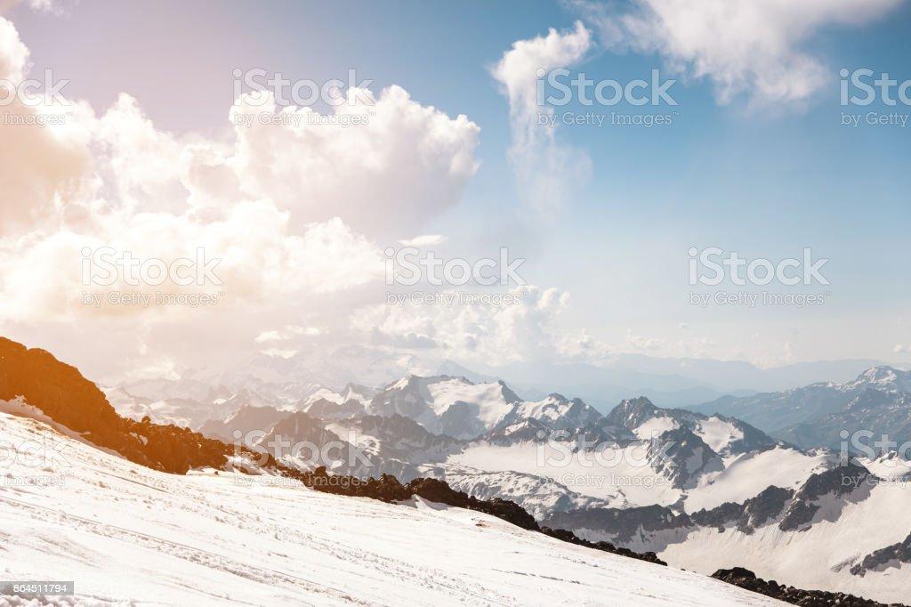 Sombre ciel bleu avec des nuages sur les sommets rocheux de la montagne couverte de glaciers et de neige - Photo