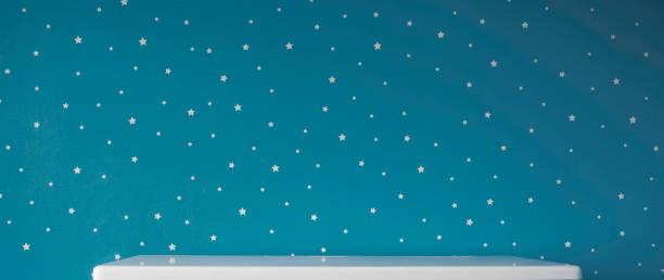 pared estrellada azul oscuro y mesa blanca vacía - foto de stock
