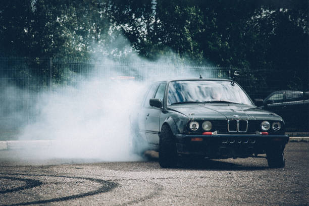 A dark BMW car drifts in the parking lot. A lot of smoke, a burnout. Illegal drift. Law violation. stock photo