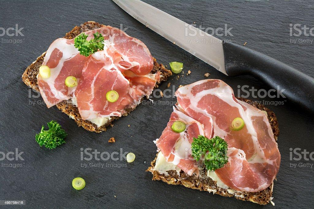 Dark bread with Italian coppa or capicola ham stock photo
