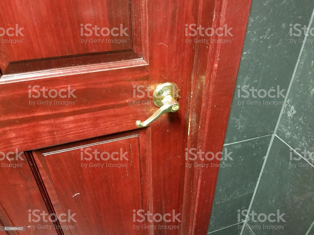 dark brown and red door with handle in bathroom stock photo