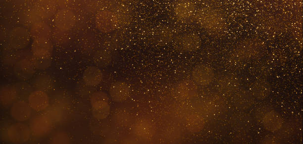 Dark brown background with golden sparkling lights Dark brown panorama background with golden sparkling lights, holiday wallpaper, copy space brown stock pictures, royalty-free photos & images