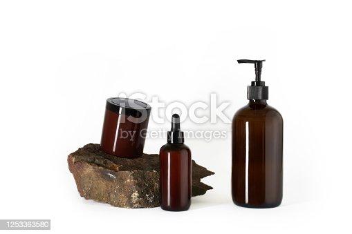 1042453716 istock photo dark brown bottles cosmetics natural stone white background isolated 1253363580