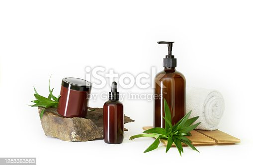 1042453716 istock photo dark brown bottles cosmetics natural stone with water lilies green leaves and white towel white background isolated 1253363583
