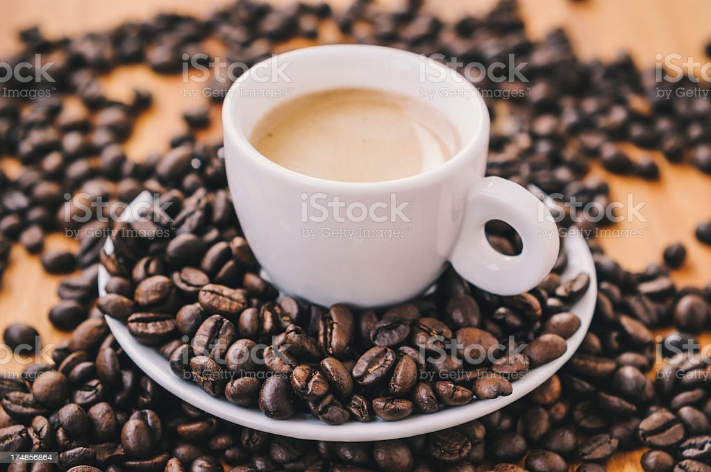Dark brown coffee beans around a cup of Espresso royalty-free stock photo