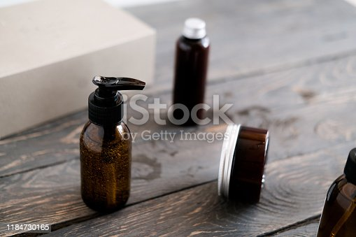 1167558793 istock photo Dark brown glass cosmetic bottles on wooden 1184730165