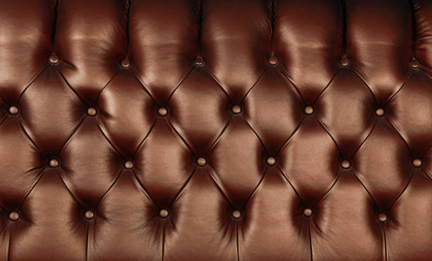 Dark brown leather capitone background texture Background texture of dark brown capitone genuine leather, retro Chesterfield style soft tufted furniture upholstery with deep diamond pattern and buttons, close up tassel stock pictures, royalty-free photos & images