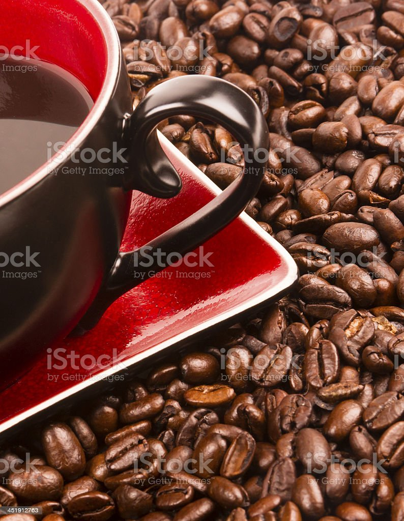 a flat pile group of roasted dark brown coffee beans with cup and...