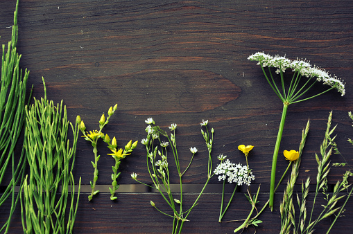 Dark brown wooden table with bunches of summer herbs and flowers.